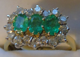 3 stone emerald and diamond ring. Fine emeralds set with white brilliant cut diamonds in 18ct yellow gold.